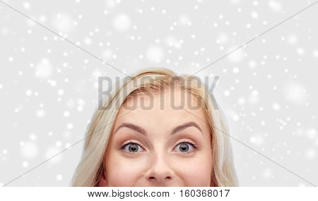 curiosity, winter holidays, christmas and people concept - happy young woman or teenage girl face over snow