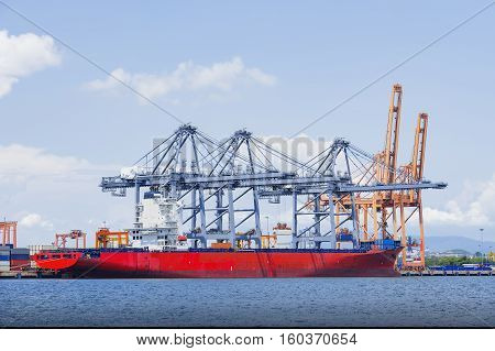 Industrial crane loading Containers in a Cargo freight shipindustrial port with containers.