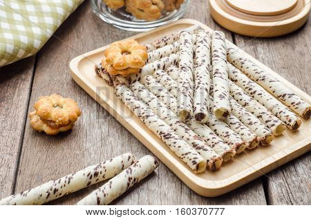 Chocolate wafer sticks and cookies on wooden table. Snack for breaking time.