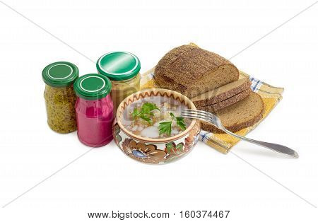 Pork aspic in ceramic bowl brown bread fork beet horseradish sauce mustard French mustard in small glass jars on a light background