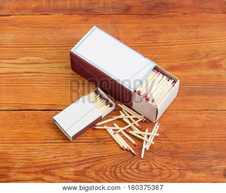 One large and one small cardboard matchboxes with household safety matches made from wood and several matches beside on a surface old wooden planks