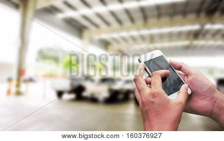 Hand hold and touch screen smart phone on abstract blur packing car for background.