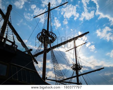 Silhouette of the ancient sailing ship on the cloudy sky background