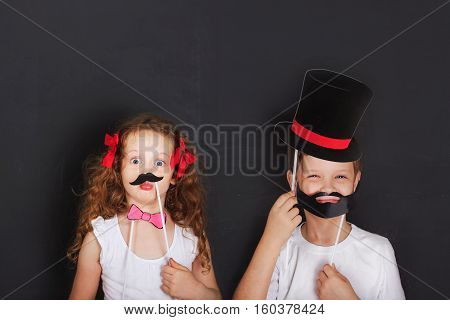 Cute twins kids hold carnival mustache and beard father day concept.