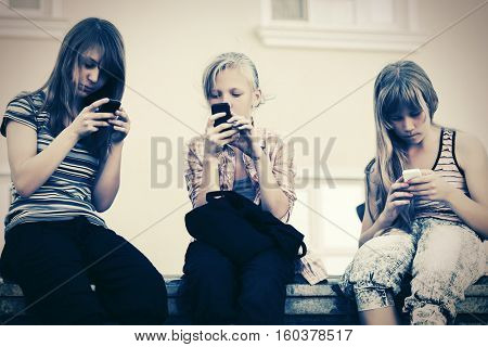 Group of teen girls calling on cell phones outdoor