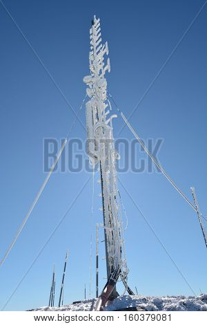 Frozen multi purpose antenna covered by hoarfrost on the mountain peak illuminated from behind