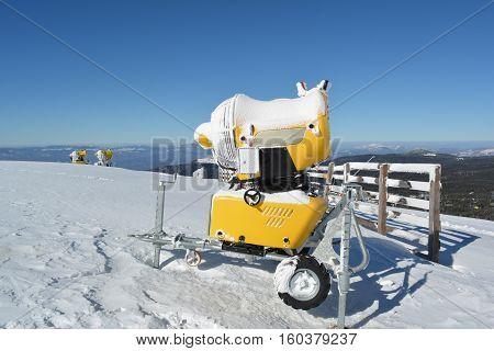 Three snow guns on the top of the mountain ready to extend ski season