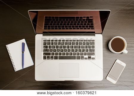 Open the laptop mug of coffee notepad and telephone on a black background top view