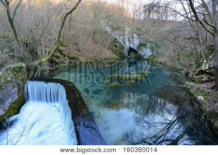 Springhead cascade and clear turquoise water of Krupaja river running out from the cave fisheye landscape Krupajsko vrelo Serbia