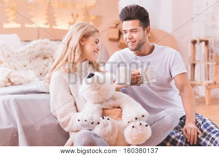 Tea time. Positive nice good looking couple sitting together and holding cups while enjoying their tea
