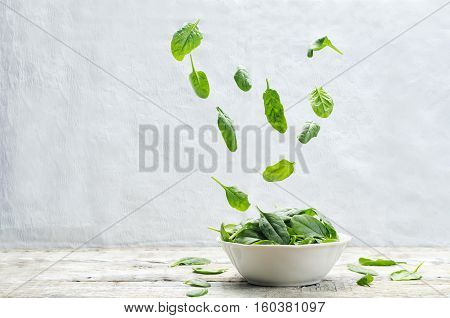 fresh flying spinach on a wood background