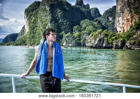 Portrait of young handsome bare chested brunet man looking away against seascape on a boat or ship, leaning on handrail
