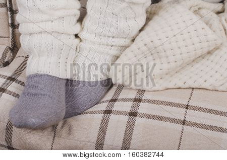 Closeup of girl's feet in warm gray socks and white leg warmers (gaiters) in winter season