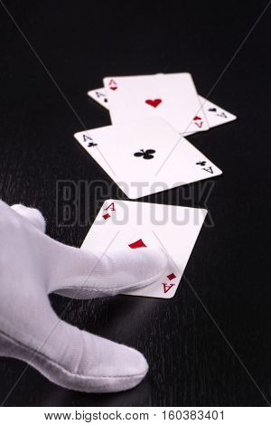 closeup hand of the dealer in white gloves in a casino handing out cards on a dark background