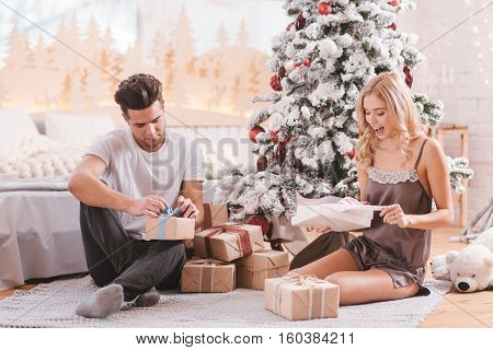 Christmas traditions. Pleasant curious delighted couple sitting under Christmas tree and unpacking their presents while having fun together
