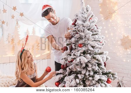 Getting ready for Christmas. Nice positive good looking couple holding Christmas decorations and decorating the Christmas tree while getting ready to the holiday