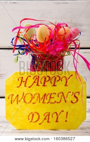 Women's Day card and candies. Streamer, sweets and greeting paper. Delicious recipe for spring holiday.