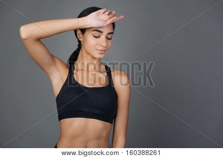 Have a break. Attractive young sporty woman putting her hand on the forehead looking down while standing against grey background