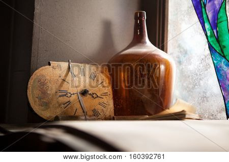 Antique Clock and the old bottle near a window and wall