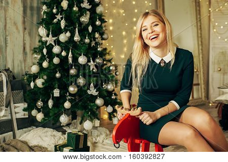 Young happy beautiful woman with gift boxes sits near Christmas tree in the room of the house. Merry Christmas and New Year.Christmas interior