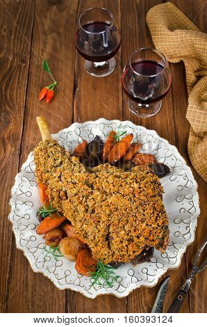 Leg of lamb baked with spicy bread crust. Roast leg of lamb with roasted vegetables in the round dish