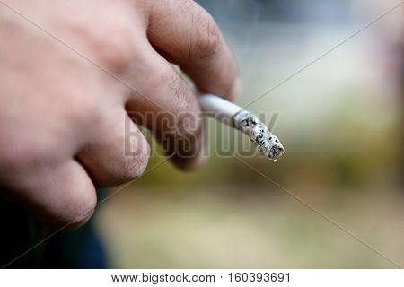 man hand holding a cigarette with smoke Selective focus.