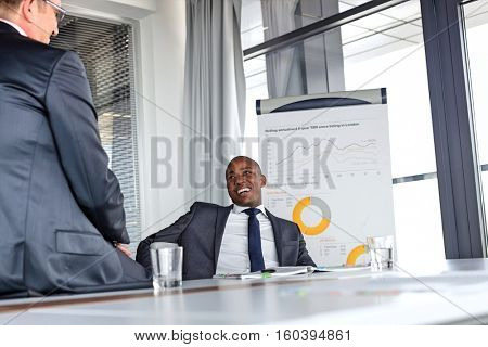 Smiling young businessman talking with male colleague in board room