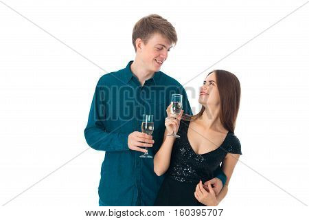 adorable young couple in love with two glasses of champagne in studio on white background