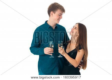 young cheerful couple in love with two glasses of champagne in studio on white background