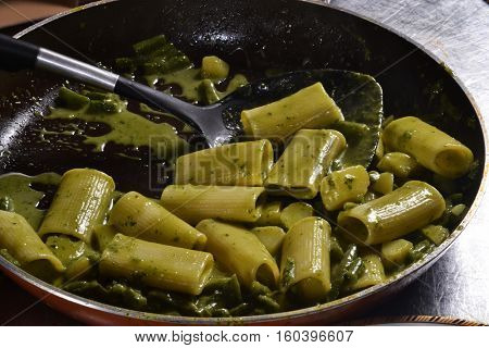 Cooking pasta with pesto sauce.