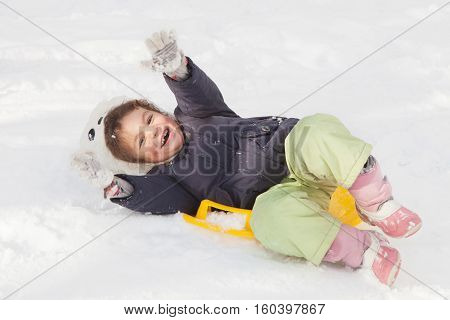 Cute little girl with saucer sleds outdoors on winter day ride down the hills overturn on sleds winter games and fun