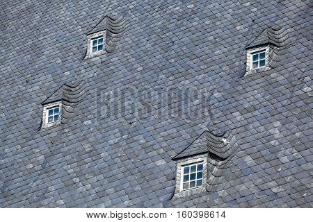 Detail of large gray slate roof and four small nice attic muntin windows (copy space)