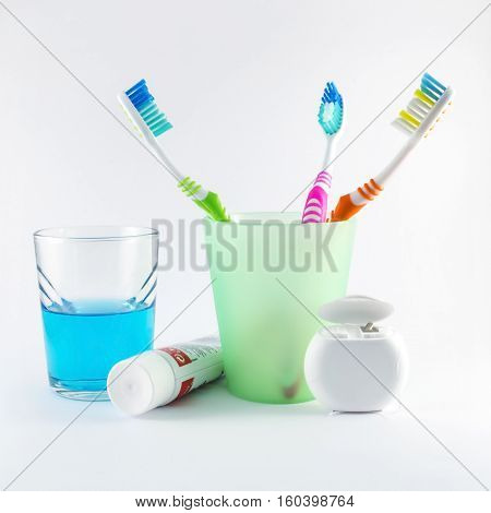 Multicolor toothbrushes, dental floss, toothpaste and mouthwash on white background