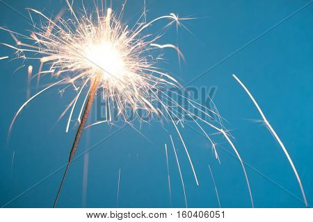 Christmas sparkler on blue background