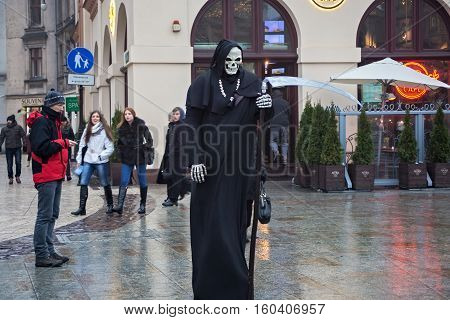 POLAND KRAKOW - JANUARY 01 2015: Living statue in the image of Death on the Main Market Square in oldtown. Krakow is the second largest and one of the oldest cities in Poland.