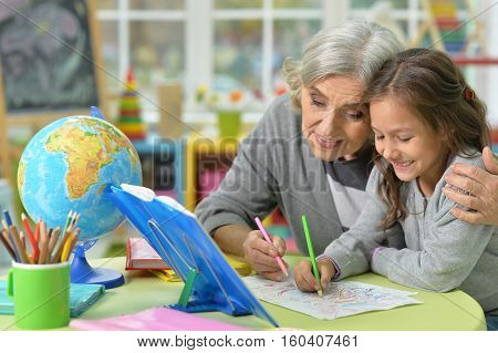 Potrait of grandmother with her granddaughter drawing