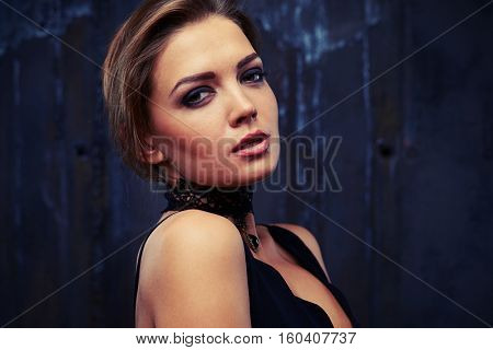 Close-up portrait of sensual young beautiful woman who turned away slightly her head with languishing look. Wearing black eveningwear and black lace necklace posing in dark studio