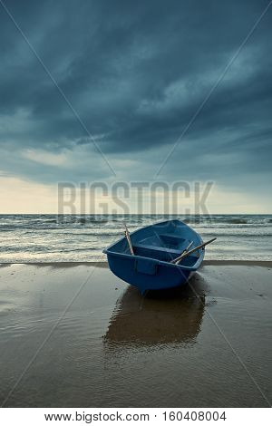 Small blue rowboat on the beach. Summer landscape