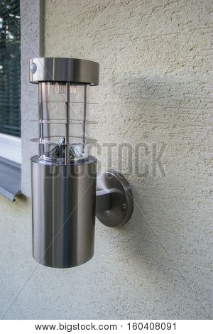 Charging Solar Outdoor Lamp Mounted On The Wall Of The House. Energy Saving Light