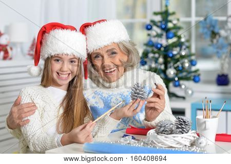 Portrait of  happy grandmother and preteen granddaughter in Santa hats preparing for Christmas