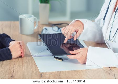 Female doctor presenting medical exam results to patient using digital tablet computer in hospital office