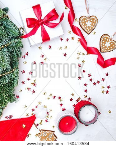 Top view Christmas composition. Xmas background ginger cookies symbol heart and home pine wreath white gift box with red fabric tape candels gold stars confetti Santa cap spiral ribbon. Holiday concept winter.