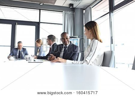 Young businessman discussing with female colleague in board room