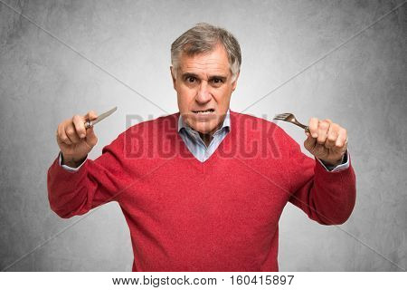 Hungry man holding fork and knife