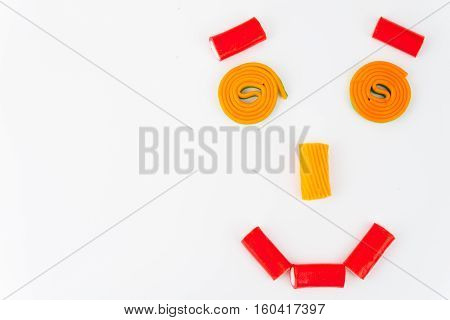 Multi-coloured candies arranged in form of funny face on white background