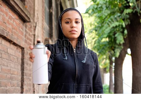 Afro-american woman using spray paint on city wall