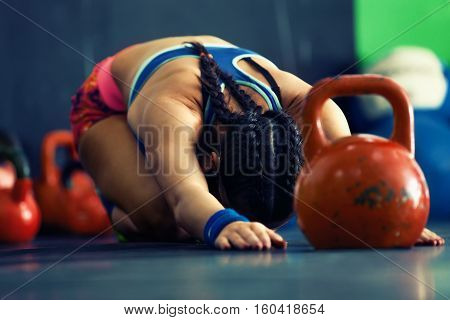 Young fitness woman training by kettlebell in gym.