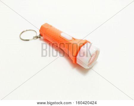 Small orange key chain flashlight on a white background.