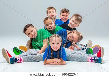 The kids dance school, ballet, hiphop, street, funky and modern dancers on gray studio background