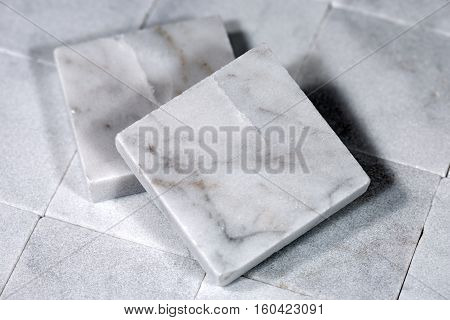 Detail of two small square tiles of white Carrara marble. Tuscany Italy